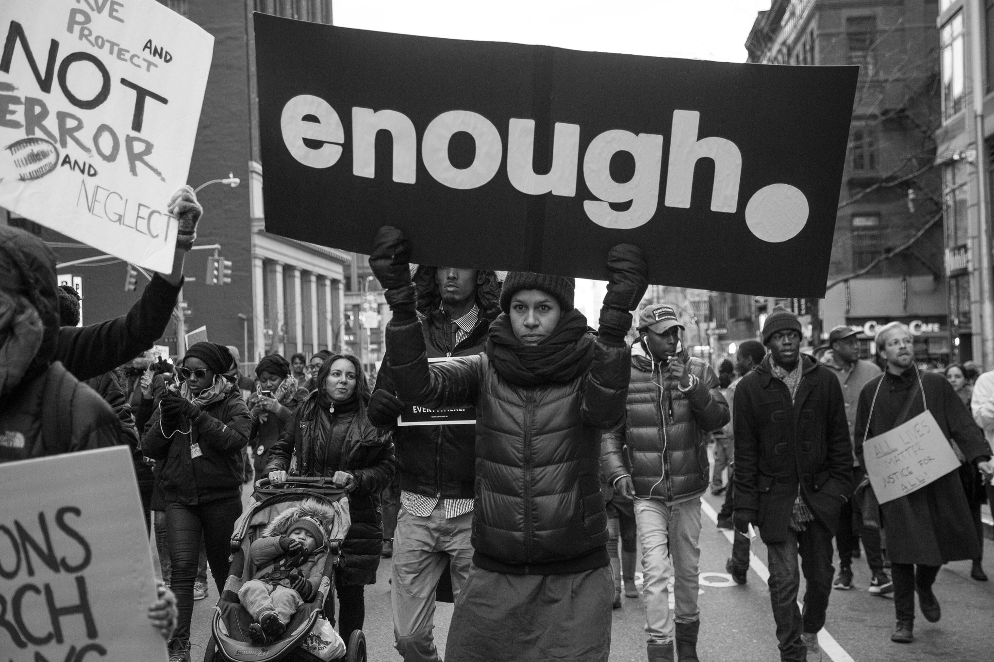 Black Lives Matter Protester carries ENOUGH sign. Photo credit Barry Yanowitz